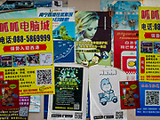 """14 FEBRUARY 2019 - SIHANOUKVILLE, CAMBODIA:  Handbills that cater to Chinese customers on a wall in Sihanoukville. There are about 80 Chinese casinos and resort hotels open in Sihanoukville and dozens more under construction. The casinos are changing the city, once a sleepy port on Southeast Asia's """"backpacker trail"""" into a booming city. The change is coming with a cost though. Many Cambodian residents of Sihanoukville  have lost their homes to make way for the casinos and the jobs are going to Chinese workers, brought in to build casinos and work in the casinos.      PHOTO BY JACK KURTZ"""