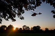 The Virgin-sponsored HEMS (Helicopter Emergency Medical Service) Explorer helicopter lands among trees in Ruskin Park, London. Used as a landing point for these helicopters has become increasingly important for head trauma patients needing to reach specialist medical teams at the nearby Kings College Hospital o Denmark Hill. As the aircraft slows and swoops its pilots put it down on empty ground to where an NHS ambulance can access the stretchered victim. London's Air Ambulance is a registered charity that runs London's only helicopter emergency medical service, serving the 10 million people who live, work and commute within the capital's M25 orbital motorway.