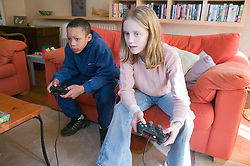 Boy and girl concentrating on playing a computer game together,