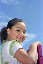 Portrait of young girl playing on climbing frame in playground smiling,