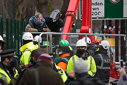 © Licensed to London News Pictures.31/01/2021, London,UK. A protestor is detained from the Euston Square Gardens in central London after protesting on a tree since Wednesday. Eco-activists are living in increasingly unstable tunnels beneath the square. Photo credit: Marcin Nowak/LNP