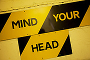 Yellow and black warning sign reads: Mind your head