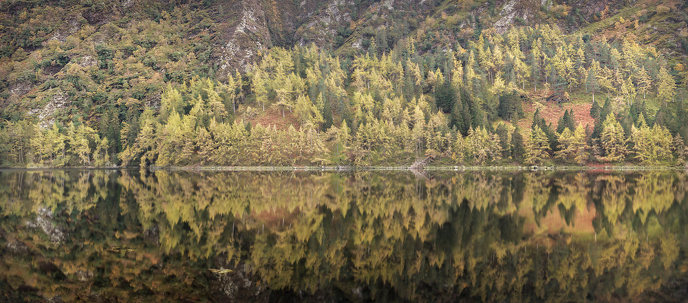 Glendalough Autumn. No wind, calm water and Autumn colors can do a lot for a landscape photograph. Here, the Autumn colors have come alive and the lake reflections add to the composition. The image is created from 14 images (2 rows of 7) shot on a tripod with a panorama head and stitched together with dedicated software.