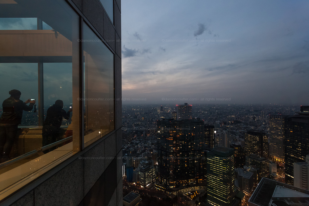 Tourists take photos, with smart phones, of the dusk sky over Tokyo from the 45th Floor Observation deck of the Tokyo Metropolitan Government Tower in Shinjuku., Tokyo, Japan. Thursday February 15th 2018
