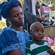 Dressed up in traditional clothing for the weekly highlight of Koumbadiouma's social calendar, a woman nurses her some at the Sunday market. Kolda, Senegal.
