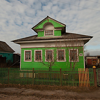 An aging, traditional Russian house stands by a road leading into the northern port of Arkhangel'sk.