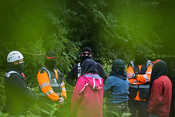 Denham, UK. 8th September, 2020. National Eviction Team enforcement agents and HS2 security guards stand in the river Colne to prevent HS2 Rebellion activists from supporting a fellow activist who had climbed a tree in Denham Country Park in order to try to protect it from works for the HS2 high-speed rail link. Anti-HS2 activists continue to try to prevent or delay works on the controversial £106bn project for which the construction phase was announced on 4th September from a series of protection camps based along the route of the line between London and Birmingham.