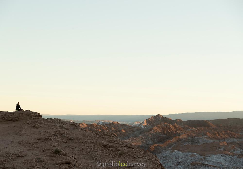 Tourist watching sunset on desert, Valle de la Luna, Atacama Desert, Chile