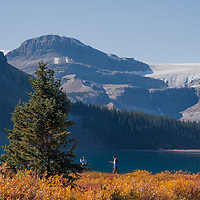 Hikers walk beside Bow Lake in Banff National Park, Alberta, Canada.  Behind is the Wapta Icefield.
