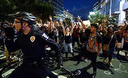September 21, 2016 - Charlotte, North Carolina, U.S. - Protestors march behind a bicycle officer along Trade Street. The protestors were rallying against the fatal shooting of Keith Lamont Scott by police on Tuesday evening in the University City area. (Credit Image: © Jeff Siner/TNS via ZUMA Wire)