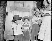 """Y-480418-06. """"Small Fry. Right up to date, younger Celilo celebrants blew bubble gum, read comic magazines"""" Indian children in the Celilo Village longhouse during the Feast of the First Salmon. Note Chief Thopson behind the door. April 18, 1948."""