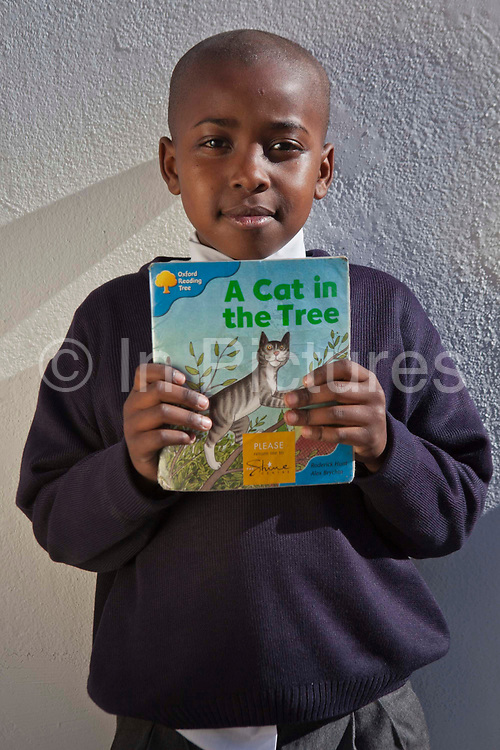 A young African school-child proudly holds his 'A Cat in the Tree' reading book outside his classroom in Zonnebloem School, Cape Town, South Africa.  He is learning to read independently.  The book has been provided provided to the school by Shine Centre which is a charity that aims to address the high illiteracy rate in South Africa by improving literacy levels among children in schools and disadvantaged communities.