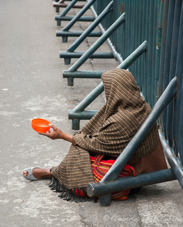 Homeless woman begging in the Zocalo, in front of the Palacio National, Mexico City / Distrito Federal, Mexico, covered in traditional woven fabrics.