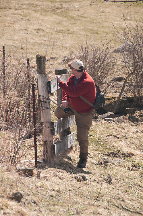 An angler uses a special gate in an agricultural fence to gain access to a stream while fly fishing in the Driftless Area of southwest Wisconsin.