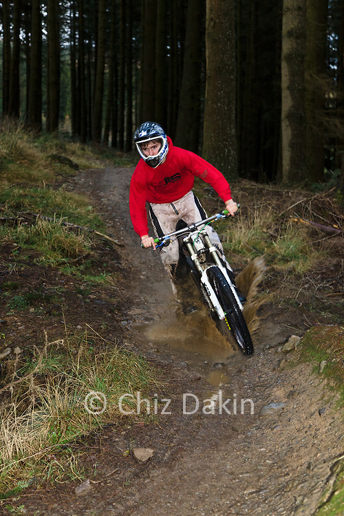 Unknown rider descending through forest and a splashing puddle on The North Face Red track at Grizedale Forest.