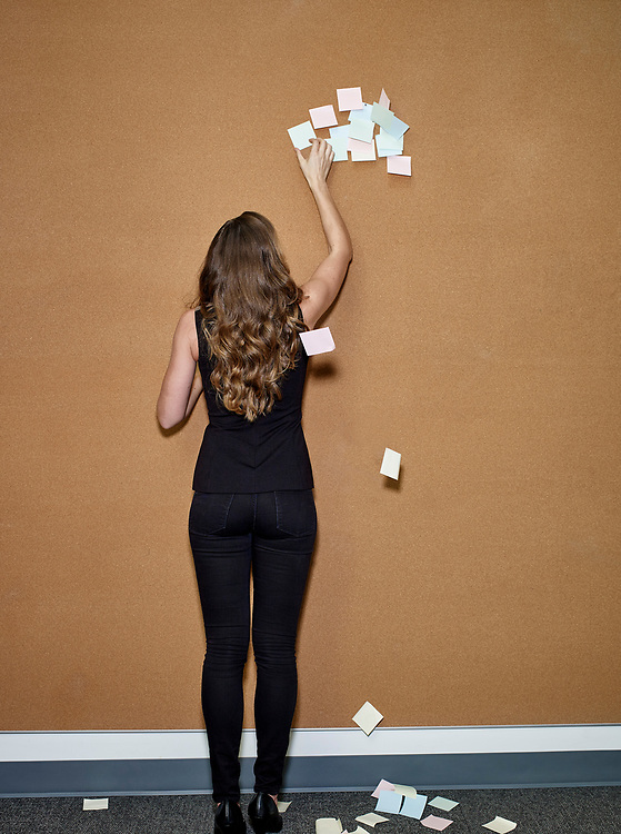 Woman, late 20's, removing post-it notes from cork office wall.