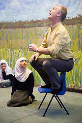 Teacher giving an entertaining assembly to children at the Nottingham Islamia school,