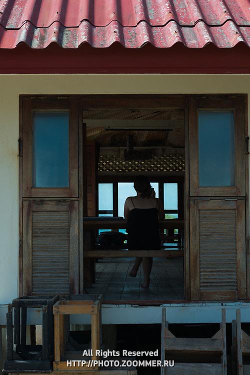 Girl through the window of Lighthouse restaurant, Phangan island, Thailand