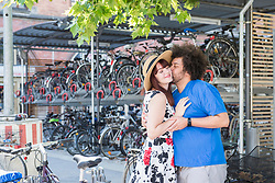 young couple kissing by bicycle parking