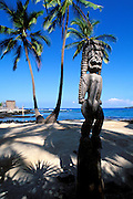 Wooden tiki and coconut palms at Pu'uhonua o Honaunau National Historic Park (City of Refuge), Kona Coast, Hawaii