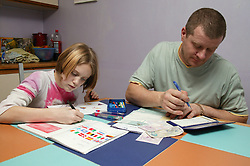 Young girl doing her homework while her father writes a cheque to pay a bill in the kitchen,