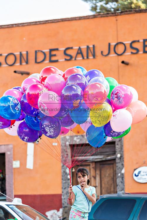 A young girl sells balloons in the Plaza de la Soledad in the historic center of San Miguel de Allende, Mexico.