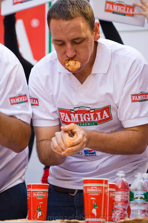 Competitive eater Joey Chestnut works his way through his 25th slice of pizza in the Famous Famiglia world championship pizza eating contest in New York City's Times Square. (Joey Chestnut is featured in the book What I Eat: Around the World in 80 Diets.) He won the $5,000 first prize after eating 45 slices of cheese pizza in 10 minutes.  Each slice weighed 109 grams (3.84 ounces) and contained 260 calories. In ten minutes Joey consumed 10.81 pounds (4.9 kilograms) of pizza and drank a gallon of water. The pizza contained 11,700 calories. MODEL RELEASED.