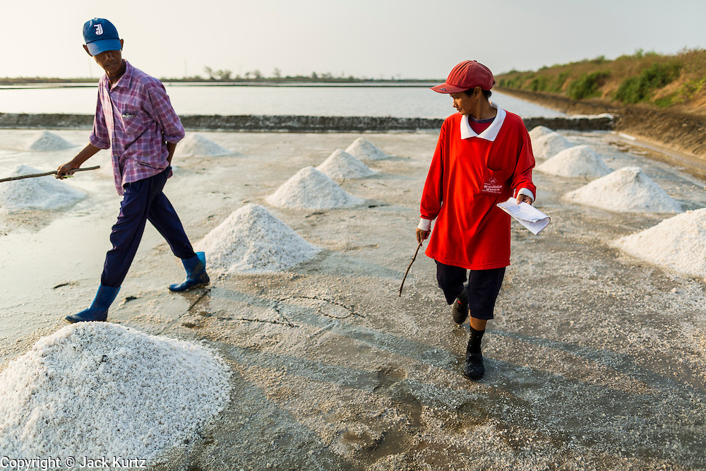 """28 MARCH 2014 - NA KHOK, SAMUT SAKHON, THAILAND: Salt farm managers inventory piles of salt in an evaporation pond in Samut Sakhon province. Thai salt farmers south of Bangkok are experiencing a better than usual year this year because of the drought gripping Thailand. Some salt farmers say they could get an extra month of salt collection out of their fields because it has rained so little through the current dry season. Salt is normally collected from late February through May. Fields are flooded with sea water and salt is collected as the water evaporates. Last year, the salt season was shortened by more than a month because of unseasonable rains. The Thai government has warned farmers and consumers that 2014 may be a record dry year because an expected """"El Nino"""" weather pattern will block rain in mainland Southeast Asia. Salt has traditionally been harvested in tidal basins along the coast southwest of Bangkok but industrial development in the area has reduced the amount of land available for commercial salt production and now salt is mainly harvested in a small parts of Samut Songkhram and Samut Sakhon provinces.    PHOTO BY JACK KURTZ"""