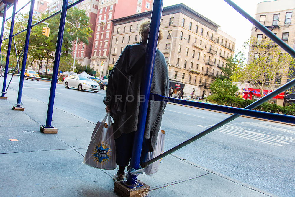 woman holding shopping bags and leaning against scaffolding in New York City
