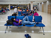 "24 DECEMBER 2015 - BANGKOK, THAILAND:  A passenger sleeps in the new domestic terminal at Don Muang (also spelled Don Mueang) International Airport. The new terminal had its ""soft"" opening Dec. 24. Don Muang is the airport used by low cost airlines serving Bangkok and is now the largest airport in the world for low cost carriers. In 2014, more than 21million passengers used Don Muang. Don Muang International Airport is the oldest airport in Asia and one of the oldest airports in the world. It started functioning as an airfield in 1914.    PHOTO BY JACK KURTZ"