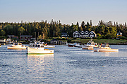 Lobster boats at sunset, moored in the quaint fishing harbor of Port Clyde, Maine.