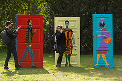 """© Licensed to London News Pictures. 07/10/2020. LONDON, UK. A couple next to """"Five Conversations"""", 2019, by Lubaina Himid at Frieze Sculpture, an annual exhibition of outdoor works by international artists in Regent's Park.  The works are on display to the public until 18 October.  Photo credit: Stephen Chung/LNP"""