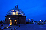 The entrance dome of the Greenwich Foot Tunnel glows in winter twilight, London.
