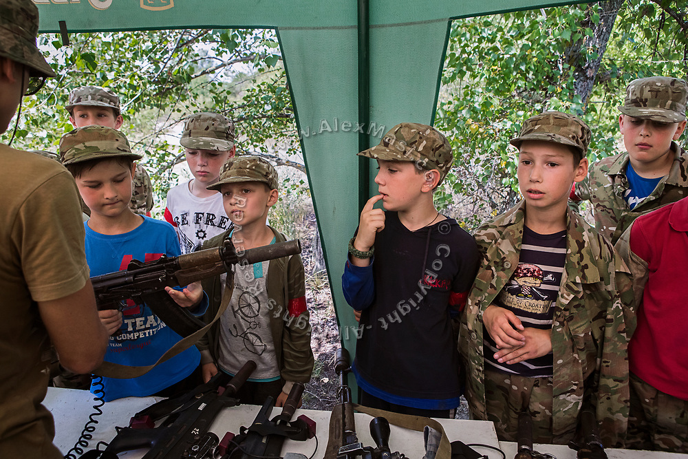Youngsters participating to the ultra-nationalistic Azovets children's camp are choosing their laser-guns ahead of a teams battle on the banks of the Dnieper river in Kiev, Ukraine's capital.