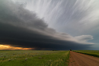 """After driving for over 5 hours I finally reached the edge of this powerful supercell just west of Faith, South Dakota. The shelf cloud looked amazing, backlit by the sunset and spitting out lots of lightning bolts. Once the storm hit it brought 1.5"""" hail which left some dents in my car."""