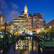 View of downtown Boston at night from Long Wharf. In the center of frame is the tall Marriot Custom House Hotel clock tower.