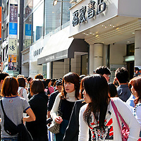 Asia, Japan, Tokyo. Young fashionable Japanese girls queue up to get in a western retail clothing store in the Ginza.