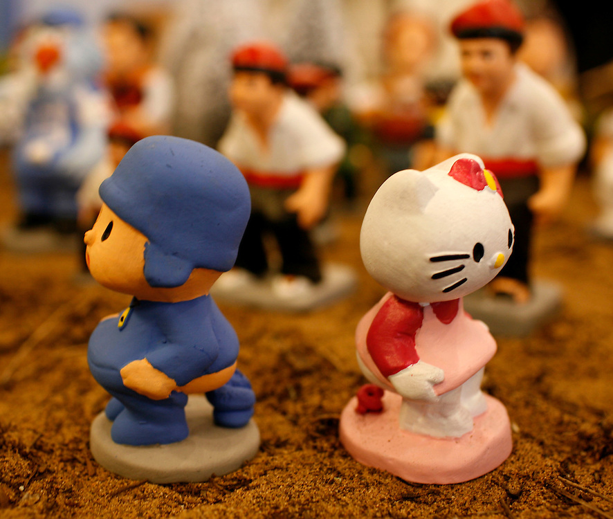 """Torroella de Mongri, Spain, 19 November 2009. .A company in Torroella de Montgrí (Girona, Spain) called """"caganer.com"""" specialized in the production of """"caganers"""" unveiled today  the new figures for Christmas as cartoon Hello Kitty..A """"Caganer"""" is a small figure from Catalonia, usually made of fired clay,  and depicted as squating person in the act defecating. .""""Caganer"""" is Catalan for pooper. It fomrs part of one of the typical figures of  the manger or """"Nativity"""" scene together with Mary, .Joseph and the baby Jesus but hidden in a corner. It is a humorous figure, originally portraying a peasant wearing a .barretina (a red stocking hat), and seems to date from the 18th century when it  was believed that the figure's depositions  .would fertilize the earth to bring a properous year. With  the course of the time, the original  personage of this pooping figure .was  substituted with personalities from the political and sports world and other famous personalities."""