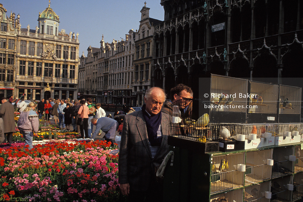 Bird fanciers admire caged tropical birds in the Grand Place (Grote Markt, in Flemish) bird market, Brussels, Belgium, on 24th June 1992, in Brussels, Belgium. In the cages are small birds from tropical countries, on sale every Sunday for those wanting avian company in their homes. The Brussels Grand Place hosts this bird market and the selection and prices are generally better than can be found in pet shops though the origins of these creatures are questionable. The Grand Place is Brussels' main city square, the focal point for colourful events throughout the year. Its Dutch-styled gabled guildhalls date from the 13th century and is now a UNESCO World Heritage Site.