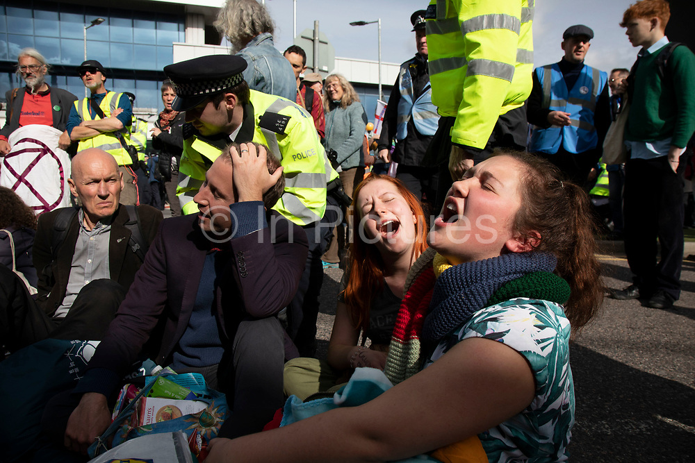 Extinction Rebellion singing songs during disruption outside City Airport on 10th October 2019 in London, England, United Kingdom. The protest is against the climate and pollution impact of the government's plans for airport expansion which will potentially double the amount of flights coming from City Airport. Extinction Rebellion is a climate change group started in 2018 and has gained a huge following of people committed to peaceful protests. These protests are highlighting that the government is not doing enough to avoid catastrophic climate change and to demand the government take radical action to save the planet.