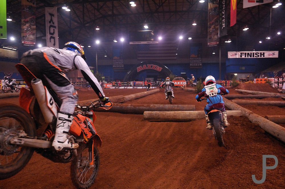 The race course had large obstacles such as telephone poles, tires and rocks to navigate.  Here several racers run down the inside straight at the 2007 Maxxis AMA Endurocross at the Lazy E Arena in Guthrie, Oklahoma.  Event was won by David Knight #101 on KTM