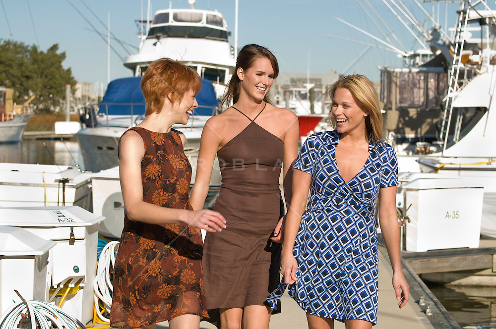 Red head, brunett and blonde women walking on a marina dock