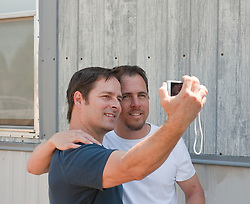 Man photographing himself with another man