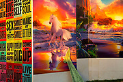 Glastonbury Festival 2014.<br /> Unicorns pasted onto the volving graphic walls by Link Leisure give a dream like quality as you enter Shangri-La<br /> Shangri-La is the after-hours epicentre of Glastonbury Festival, a largely indescribable, ephemeral and interactive world that really comes to life after dark.<br /> Unique among festivals, Shangri-la has a central narrative that pins it all together,  it evolves year by year (a bit like Star Wars). All contributors respond to this narrative, and add to it via their installations, venues and performances. When it all comes together on site the audience have a wholly immersive world to become lost in with a myriad of places to explore.<br /> Exploration and discovery is an important aspect of  Shangri-la. A maze of covered alleys is riddled with nano-venues, performers and installations, artworks and hidden doors.<br />  In 2014 Shangri-La explored the way we create heavens and hells for ourselves.