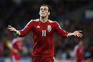 Gareth Bale of Wales signals for support from the Welsh fans. Euro 2016 qualifying group B match, Wales v Bosnia- Herzegovina at the Cardiff city Stadium in Cardiff, South Wales on Friday 10th Oct 2014.<br /> pic by Andrew Orchard, Andrew Orchard sports photography.