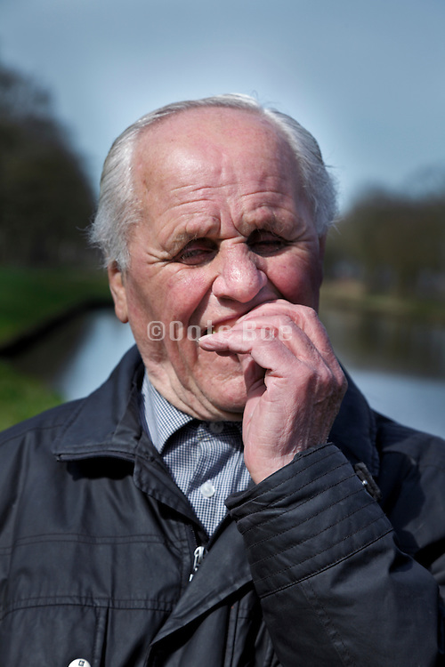portrait of senior 88 year old man putting dentures in his mouth