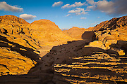 A jeep is parked in a remote desert valley at sunset in Wadi Rum, Jordan.
