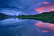 The last ray of sunlight reaches under the clouds after a storm at Oxbow Bend along the Snake River in Grand Teton National Park, Jackson Hole, Wyoming