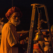 A Hindu man rings a ceremonial bell during Ganga aarti along the banks of the Ganges River at Triveni Ghat, Rishikesh, Uttarakhand, India.