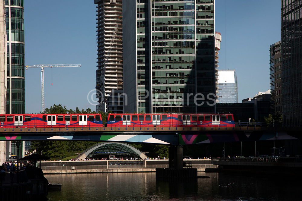 DLR train on elevated tracks crosses Middle Dock into the Canary Wharf financial district in London, England, United Kingdom. Canary Wharf is a financial area which is still growing as construction of new skyscrapers continues. The Docklands Light Railway is an automated light metro system opened in 1987 to serve the redeveloped Docklands area of London.